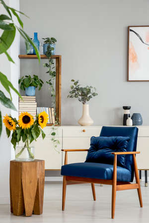 Sunflowers on wooden stool next to blue armchair in living room interior with poster. Real photo Stok Fotoğraf - 107026673