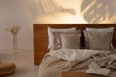 Pouf and flowers next to bed with headboard and pillows in bedroom interior with book. Real photo Archivio Fotografico - 107026685