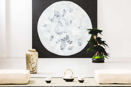 Moon poster and bonsai between pillows on the floor in japanese dining room interior. Real photo with blurred background