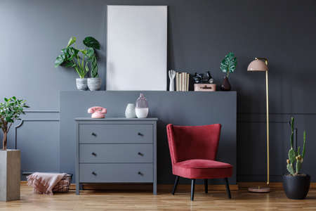 Real photo of a red armchair standing next to a chest of drawers and a lamp in a living room interior with plants and ornaments. Empty poster with a place for your graphic