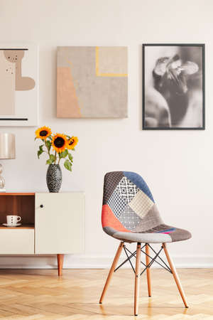 Modern chair in white apartment interior with posters above cupboard with sunflowers. Real photo