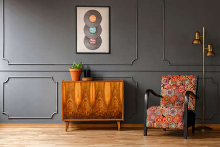 Real photo of wooden retro cupboard with fresh plant and candle standing in dark grey living room interior with colorful armchair, gold lamp and poster with vinyls