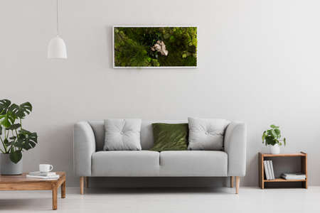 Grey sofa with pillow in real photo of bright sitting room interior with books on wooden shelf, coffee cup on table and garden in frame hanging on the wall Stockfoto