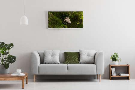 Grijze bank met kussen in echte foto van lichte woonkamer interieur met boeken op houten plank, koffiekopje op tafel en tuin in frame opknoping aan de muur