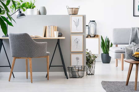Foto real de silla gris de pie junto al escritorio de madera con libros en media pared con bocetos simples en el interior luminoso de la sala de estar Foto de archivo