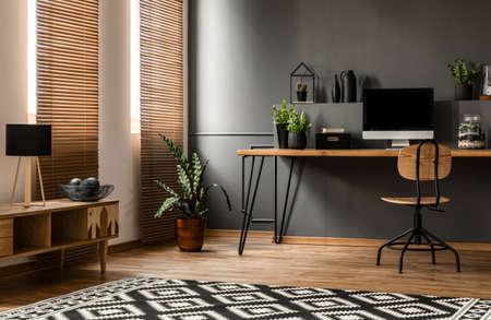 lámpara en el armario de madera cerca de la planta y el escritorio con monitor de ordenador portátil en el interior de la sala de trabajo de color gris oscuro