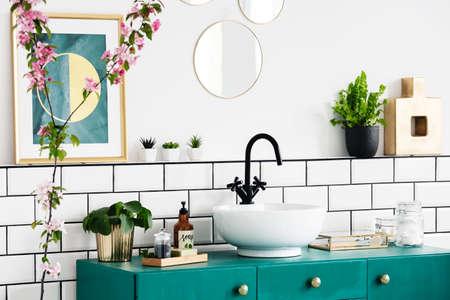 Primer plano de una flor, gráfico en la pared y lavabo sobre un armario turquesa. Foto real