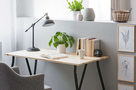 Echte foto van een houten bureau met verse plant, zwarte lamp, koffiekopje en boeken die op een halve muur staan met eenvoudige posters