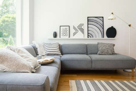 Real photo of white Scandi sitting room interior with metal lamp, corner sofa with cushions and modern art posters