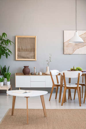 Real photo of an open space dining room with wooden table and chairs next to a simple cupboard and a coffee table on a natural rug Stock Photo
