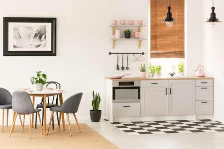 Echtes Foto des offenen Innenraums der Küche mit Esstisch mit Stühlen, Fenster mit Holzjalousien und rosa Accessoires auf Arbeitsplatte Standard-Bild