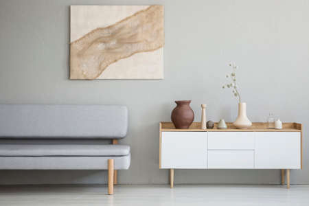 Real photo of a simple living room interior with a natural painting on the wall and gray sofa next to a wooden cupboard Stock Photo