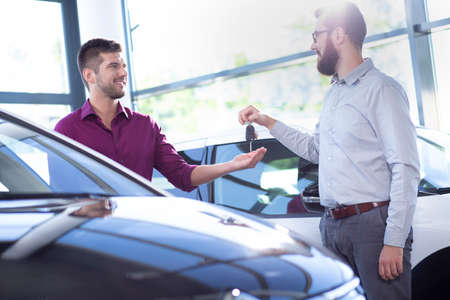 Smiling car dealer giving keys to new buyer in a dealing salon