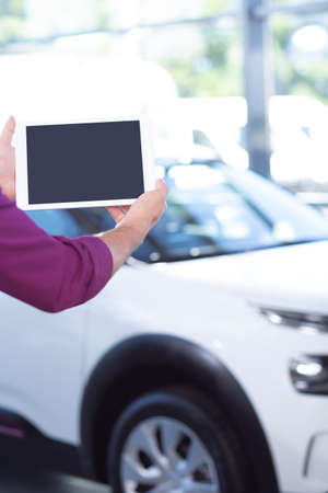 Mockup of sellers tablet in car showroom with exclusive vehicles 写真素材