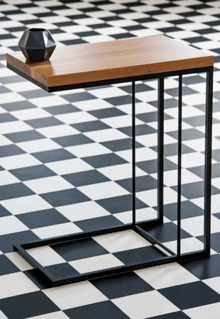 Real photo with close-up of wood and metal end table with black geometric small vase standing on checkerboard floor