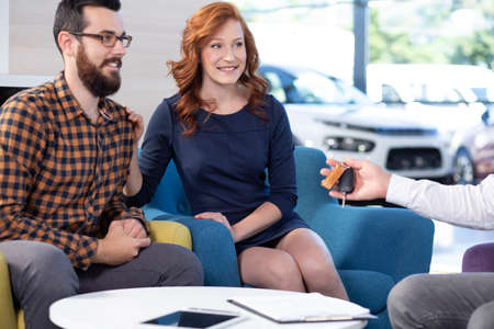 Smiling and happy marriage buying a new car in exclusive showroom