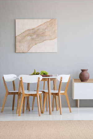 Real photo of a natural, scandi dining room interior with a round, wooden table and white chairs standing against light gray wall