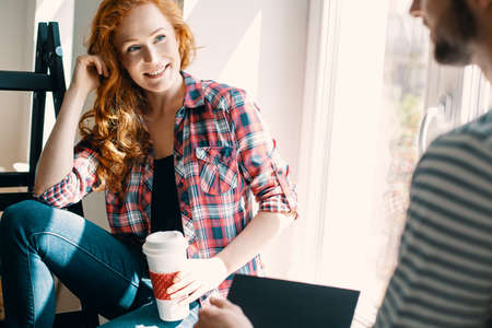 Smiling red haired woman drinking coffee and talking with friend at home Stockfoto