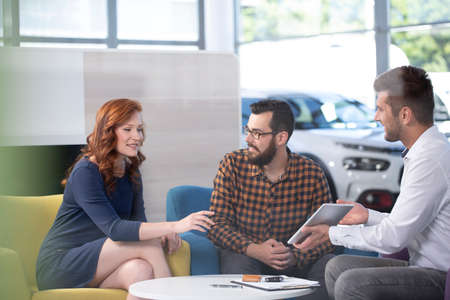 Professional car dealer offering luxurious vehicles during meeting with buyers in salon