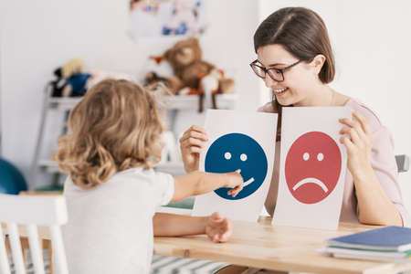 Young kid pointing at graphic with a smiley face during a psychotherapy session