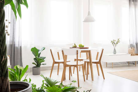Real photo of a bright, scandi dining room with a white lamp above a round table with wooden chairs, next to the window