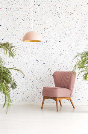 Single armchair, chandelier and leaves of plants set on a dotted wall in hotel lobby interior. Real photo Stock Photo