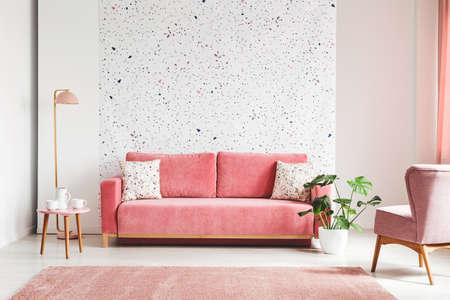 Prawdziwe zdjęcie różowej, aksamitnej sofy, rośliny, stolika kawowego z garnkiem i filiżankami na ścianie lastrico wnętrza salonu