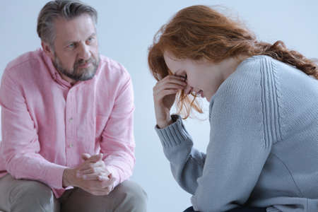 A redheaded young woman with a post traumatic stress disorder touching her eyes with her hand during an individual psychotherapy session with a specialist. Stock Photo