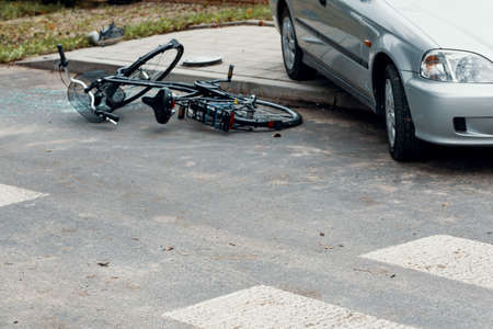 Broken bicycle and car on the road after dangerous collision Stock Photo