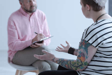 A tattooed rebel adolescent girl with mental and behavioral disorders in a psychiatry office during an evaluation meeting with a specialist.
