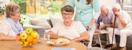 Panorama der glücklichen behinderten älteren Frau und der Krankenschwester, die ihr helfen
