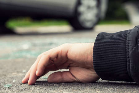 Close-up of a hand of dead person after collision with a car on the road