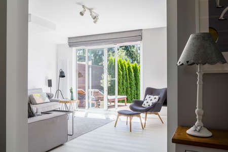 Lamp on cabinet and windows in white living room interior with grey armchair and sofa. Real photo Stock Photo
