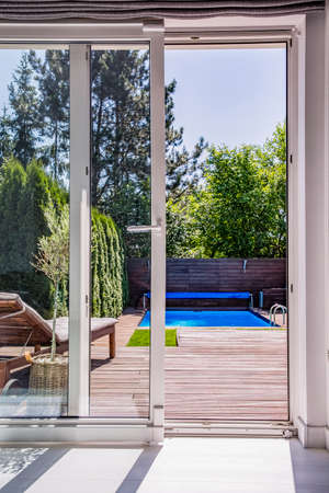 View through window on terrace with sunbed, swimming pool and trees. Real photo