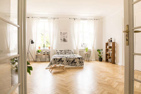 View through an open double door into a bedroom interior with wooden parquet, large windows and white walls. Bed with linen, breakfast tray, lamp and bookcase in the room. Real photo. Stock Photo