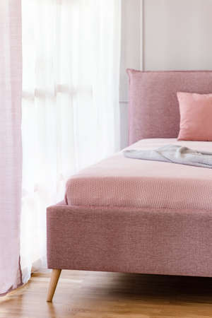 Dirty pink, comfy bed by a window with sheer curtains in a bright bedroom interior