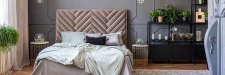Draps sur lit avec tête de lit à l'intérieur de la chambre gris et or avec des plantes. Vrai photo