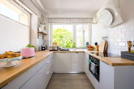 Windows in white kitchen interior with grey cabinets and wooden countertop. Real photo Stock Photo