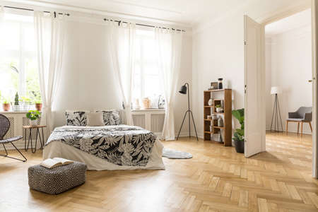 View at two rooms with white walls and herringbone parquet. A bed, a pouf, lamp bookcase and armchair in a natural style apartment interior. Real photo. Standard-Bild