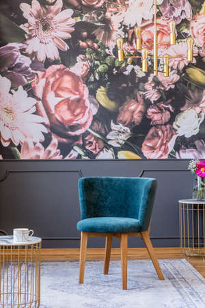Blue upholstered chair with wooden legs on a gray rug in an elegant living room interior with floral print wallpaper
