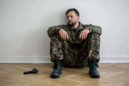 Tired professional soldier in green uniform sitting on the floor next to a gun