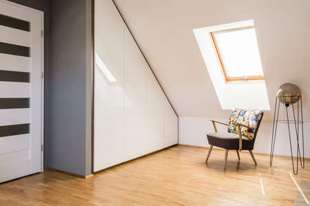 Lamp next to armchair on wooden floor in white attic interior with door and window. Real photo