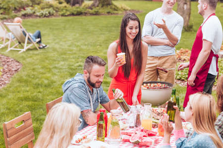 Friends at a garden BBQ party during summer school brake. Stock Photo