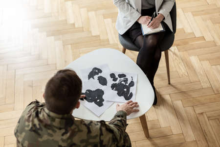 High angle on soldier choosing picture during meeting with psychiatrist