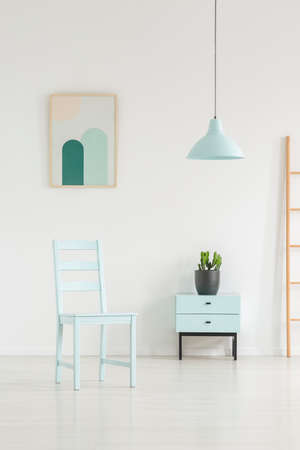 Sky blue living room interior with a chair, cabinet, lamp and painting. Real photo