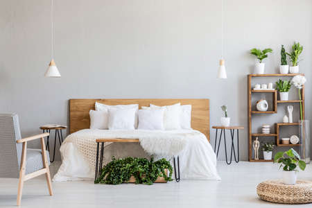 Patterned armchair near white wooden bed in grey bedroom interior with pouf and plants. Real photo Archivio Fotografico - 107107925
