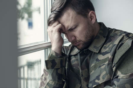 Depressed and lonely soldier in military uniform with war syndrome