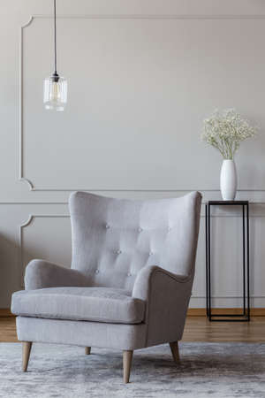 Light gray, elegant armchair and a black vase standing in a sophisticated living room interior with molding on beige walls Foto de archivo - 107107936