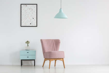 Cupboard, armchair, poster and lamp on a white, empty wall in a living room interior. Real photo. Place your table here