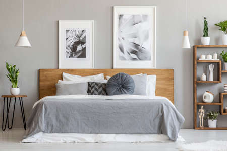 Grey sheets on wooden bed next to table with plant in bedroom interior with posters. Real photo Stock Photo